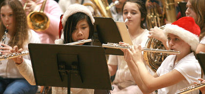 In the foreground, Tessa Hillman and Brianna Morris share a music sheet.