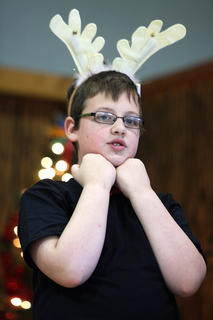 Steven McDonald, wearing some cute reindeer antlers, performs with his classmates.