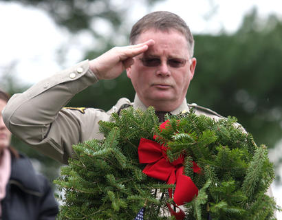 In honor of fallen Deputy Anthony Rakes, Marion County Sheriff Jimmy Clements salutes a remembrance wreath in honor of the 93,129 United States servicemen from all branches of the service who last know status ere either Prisoners of War or Missing in Action.