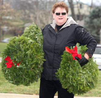 A volunteer helps carry wreaths at the Lebanon National Cemetery.
