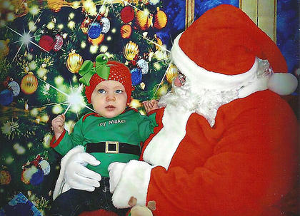 Adalyn Zora Higdon poses for her first photo with Santa Claus. She is the daughter of Matthew and Jenny Higdon.