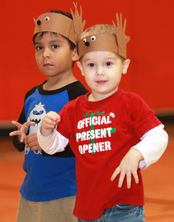 """Preschoolers Max Castillo, left, and the """"official present opener"""" Aiden Knopp get in the holiday spirit."""