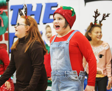 Brooklyn Whitehouse & Josie Essex, West Marion Elementary, gives a big cheer as Santa's elves.