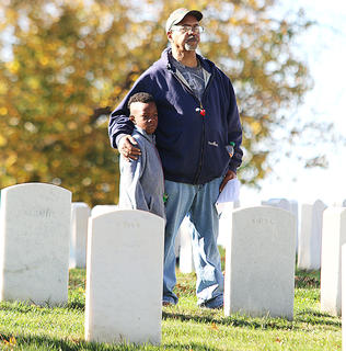 Curtis Hayden holds onto his grandson Jaytavion Cowherd as they listen to Lieutenant Colonel Allen H. Boone speak during the Veterans Day ceremony at the Lebanon National Cemetery. Hayden's father was a World War II veteran, and he said he was attending the ceremony to pay his respects to his father.