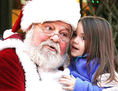 Sophia Romero, 3, of Springfield whispers her Christmas wish list to Santa Claus on Main Street in Lebanon.