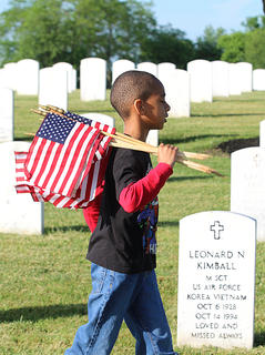 Zakais Newby volunteers with the Boy Scouts, Pack 90, at the Lebanon National Cemetery on May 23 in honor of Memorial Day.