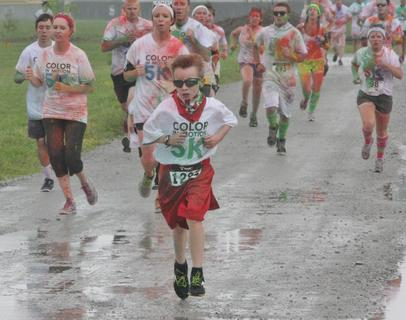 A young boy with a cape leads a group of runners toward the finish line at the Color in Motion 5K event Saturday morning.