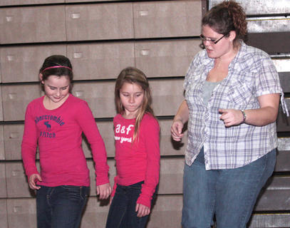 Layla Cambron and Abigail Mattingly learn a few dance steps Friday evening from Stephanie Knifley.