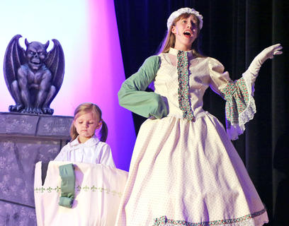 "Jessica Thomas, right, playing the part of Mrs. Potts, sings ""Beauty and the Beast"" as Carly Hill, playing the part of Chip, stands closely and listens."
