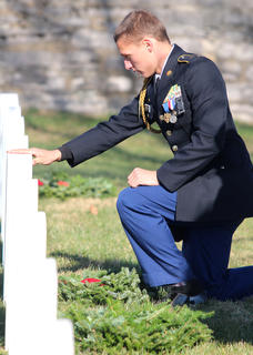 "While placing wreaths at Lebanon National Cemetery Saturday, Nathaniel ""Nate"" Hoppes, 15, takes a moment to pay his respects at each grave. Hoppes is a member of the Marion County High School Jr. ROTC program."