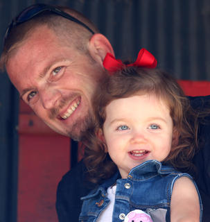 Skyler Elizabeth Mattingly shows off her beautiful baby blue eyes during the Little Miss Ham Days competition on Saturday morning. Also pictured is her father.