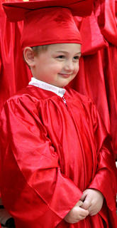 Sawyer Wheatley, 3, grins sheepishly as he performs during the preschool graduation ceremony.