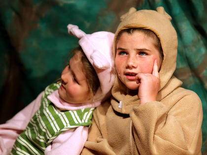 Winnie the Pooh, played by Mya Kehm, tries to come up with a plan to retrieve honey out of a tree as Piglet, played by Sophie Ballard, takes a nap.