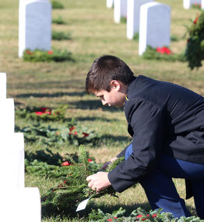 Vincent Battcher helps place wreaths at the Lebanon National Cemetery Saturday. Battcher is a member of the Marion County High School Jr. ROTC program.