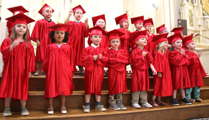 Dressed in bright red caps and gowns, the 3-year-old preschoolers perform during St. Augustine's graduation ceremony Friday afternoon.