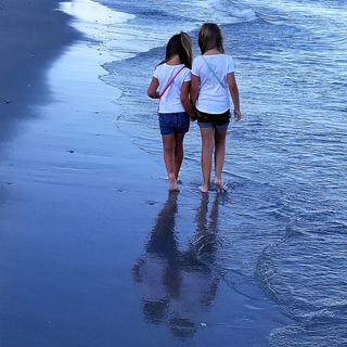 Sisters Layla and Karlee Followell enjoy time together walking the beach in Myrtle Beach, South Carolina.