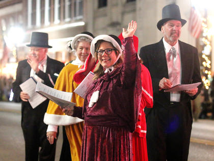 Michelle Mattingly waves to the crowd as she and a group of Christmas carolers entertain people during Dickens Christmas Friday evening. Also pictured are Wendell Luckett, Nancy Luckett, Frank Reynolds, Sue Reynolds and Charlotte Nellis.