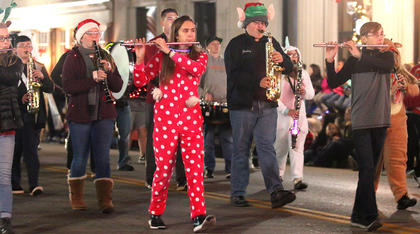 The Marion County Marching Knights march down Main Street as they perform, some of them in long pajamas, during the Dickens Christmas Parade Friday evening.