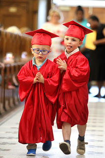 Hudson Shields, left, and Kash Simmerman, see who can make it down the aisle first during the preschool graduation ceremony at St. Augustine Catholic Church Friday afternoon.