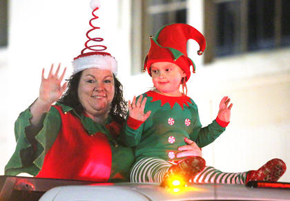 Kristen Newton and Rylee Godesa ride on the B&D Pressure Washing truck during the Dickens Christmas Parade.