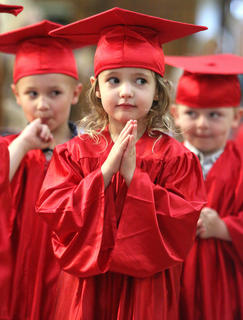 Claira DeAtley, 3, quietly stands in anticipation during St. Augustine's preschool graduation ceremony. Also pictured are Nolan Gordon and Jacob Hill.