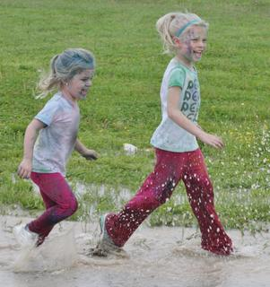 Two young participants loved splashing in the water puddles near the finish line of the Color in Motion 5K event Saturday morning.
