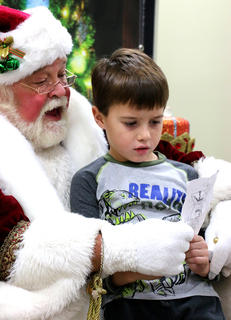 Landon Mattingly, 6, brought a hand-written list to review with Santa Claus Friday evening. He is the son of Dustin and Jessica Mattingly of Lexington.
