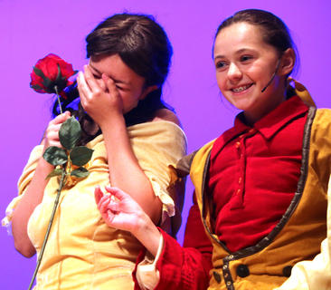 Belle, left, being played by Madison Knopp, gets tickled while on stage during a dress rehearsal Thursday. Also pictured is Aubrey Mealey playing the part of Gaston.
