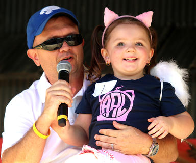 Adalyn Leigh Abell, 3, smiles at the crowd as she sits on emcee Jeremy Bowman's lap during the Little Miss Ham Days competition. She is the daughter of Phillip and Jodi Abell.