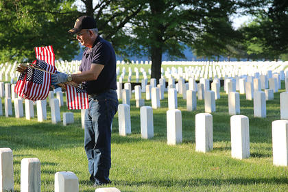 U.S. Army Veteran Marvin Cecil of Loretto helps decorate graves at the Lebanon National Cemetery Saturday morning, May 25.