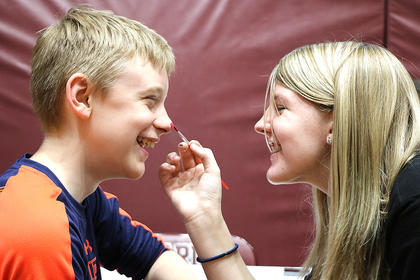 Kassidy Mattingly, right, and Austin Coffey share some laughs as she paints his face during the Working The Puzzle for Autism Inc. event in April.
