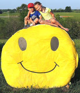 """Happy Hay Bale Summer Days""      Pictured are Linsey and Landon Craig on top of a decorated hay bale created by their ""Pappy"" (Donnie Miles). It is on the farm of Donnie and Nancy Miles in St. Francis. The kids love climbing on the bale and visiting to see what new character or theme he has decorated it as."