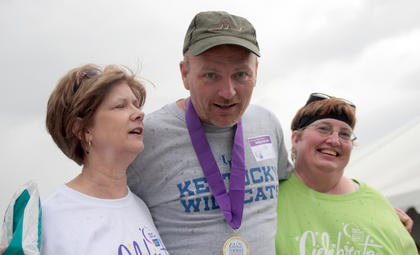 Cancer survivor Mike Ford walks arm-in-arm with Mary Ann Mattingly, left, and Donna Peterson, right, during the caregivers lap.