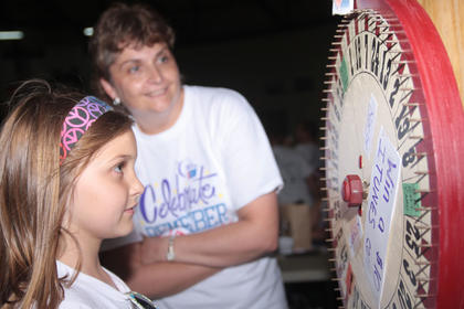Because of the rain, the event moved indoors to the Roby Dome at Marion County High School. Kaylee Buckman of St. Joe spins the wheel at the Glasscock Elementary School team's booth in hopes of winning a iTunes gift card.