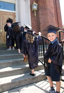 Kingston Simmerman, 4, takes a moment to smile for the camera as he and his classmates file into St. Augustine Catholic Church for the preschool graduation ceremony.