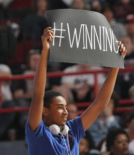 With a few minutes left in the game and the Lady Knights ahead by several points, a band member holds up a winning sign.