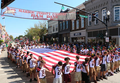 The Marion County High School football team and youth football league players carried the American flag at the start of the Pigasus Parade.