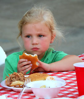 Madeline Sapp takes a moment to catch her breath while chowing down at the Pigout on Proctor Knott Avenue Thursday evening.