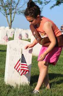 Girl Scout Emerson Osbourne, 8, decorates graves at the Lebanon National Cemetery Saturday morning, May 25. She is a Girl Scout with Troop 400.