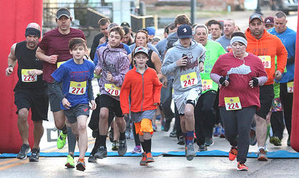 The runners at the All Fired Up About Baseball 5K take off from the finish line Saturday morning.