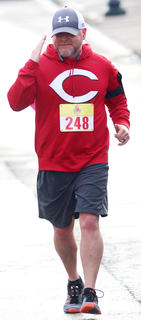 Trent Vaughn gives a salute crossing the finish line in the All Fired Up About Baseball 5K on Saturday.