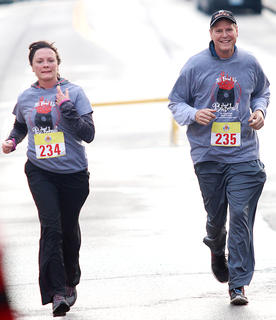 Margaret Smith (left) and her husband Bob Smith (right) finish the All Fired Up About Baseball 5K on Saturday together.