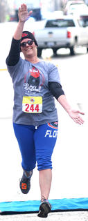 Leslie VanWhy celebrates as she crosses the finish line in the All Fired Up About Baseball 5K on Saturday.