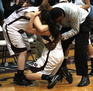 Bre Elder collapses in the arms of her teammates and assistant coach Robert Spalding after winning the 5th Region Tournament for the second year in a row.