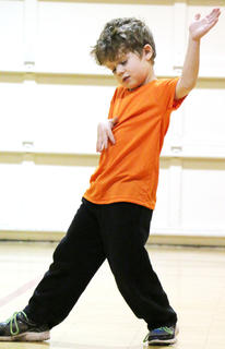 """Ethan Mullins plays the air guitar as he and his siblings, Jenna and Alex, perform a routine to """"Jailhouse Rock."""""""