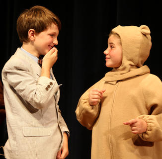 Christopher Robin, played by Jackson Hayes, and Winnie the Pooh, played by Mya Kehm, share a laugh on stage.