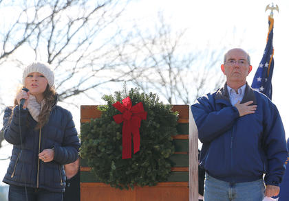 Layla Spring, left, sings the National Anthem as Hayden Johnson, organizer of the local Wreaths Across America event, holds his hand to his heart.