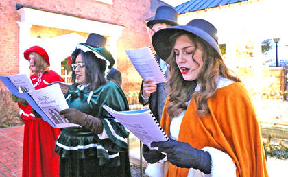 Gaubrie Humphress, Alia McClendon and Emma Humphress strolled the streets Friday evening singing Christmas carols. Not pictured are Joseph Mattingly and Caleb Miller.