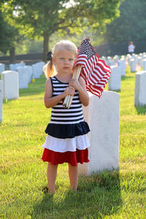 One of the Bradshaw twins (either Kendall or Klaire) holds a bundle of American flags as she helps decorate graves at the Lebanon National Cemetery on May 25. Not pictured is her twin sister and her five-year-old sister, Katie, all of Lebanon.