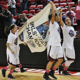 Four Lady Knights take the championship banner for a victory lap.